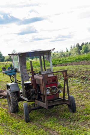 old tractor: The old tractor works in the field in the summer.