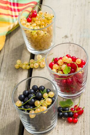glass containers: Variety of garden currant in glass containers on old wood table.