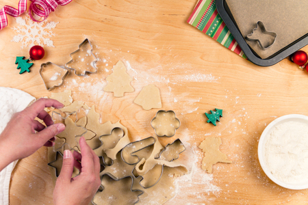 making christmas cookies with different shapes of cookie cutters stock photo - Making Christmas Cookies