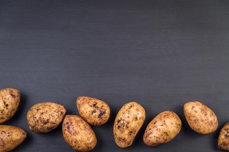 Fresh  harvested organic potatoes on a black background.