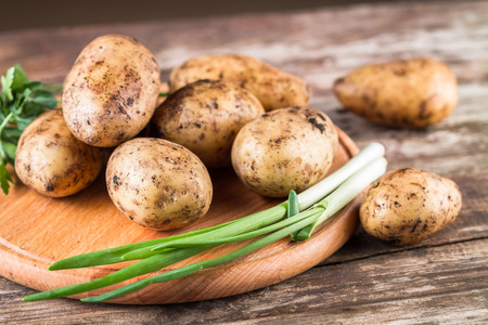 russet potato: Fresh  harvested organic potatoes on a round chopping board.