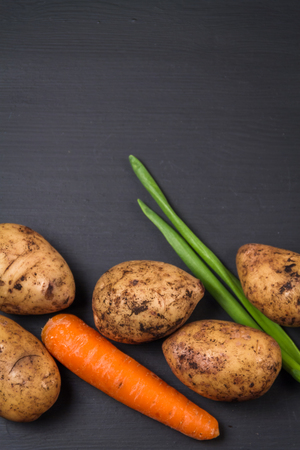 Fresh organic potatoes, carrots and green spring onions on a black background.