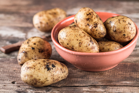Fresh harvested organic potatoes in a bowl on the wooden table. 版權商用圖片