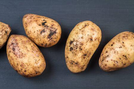 russet potato: Fresh  harvested organic potatoes on a black background. Closeup. Stock Photo
