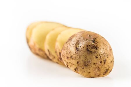 One ripe sliced potato on a white background. Close up.