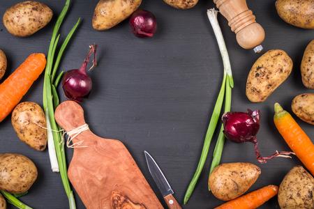 russet potato: Fresh organic potatoes, carrots and onions on a black background.