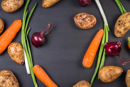 Fresh organic potatoes, carrots and onions on a black background.