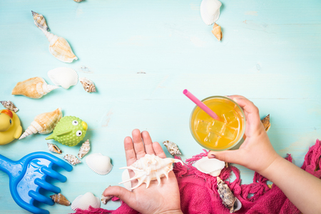 Little girl holding juice and sea shells. Top view.