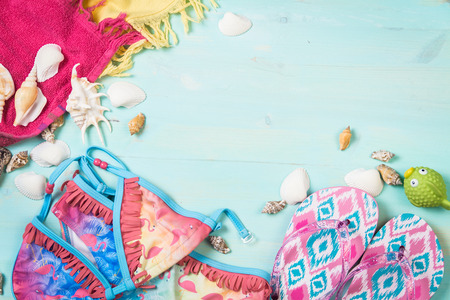 Little girls beach clothes with sea shells on a blue background. Top view. 版權商用圖片