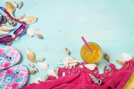 Little girls beach clothes with sea shells on a blue background. Top view. Stock Photo