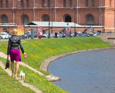 the girl with a dog goes along the channel photo