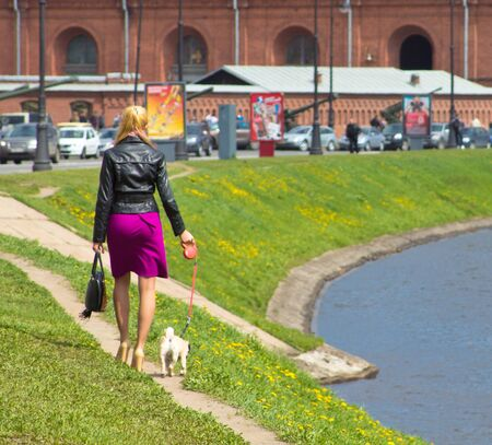 the girl with a doggie goes along the channel photo