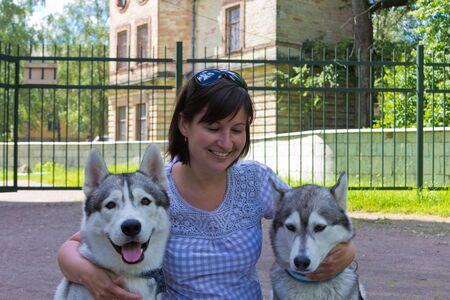 the woman embraces two dogs photo
