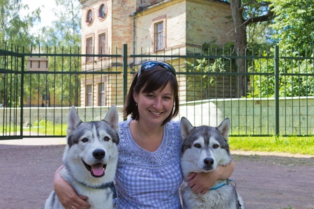 the woman embraces two dogs