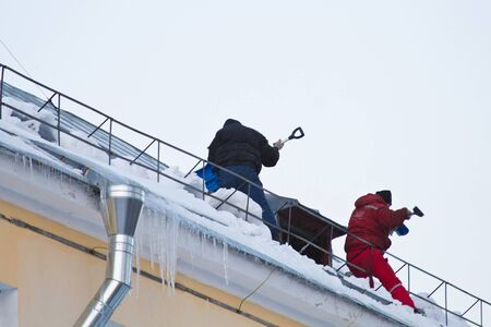 Cleaning snow from the roof Stock Photo