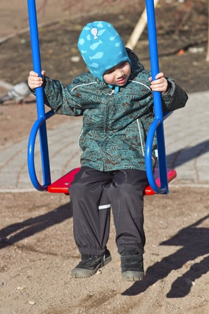little boy riding on a swing photo