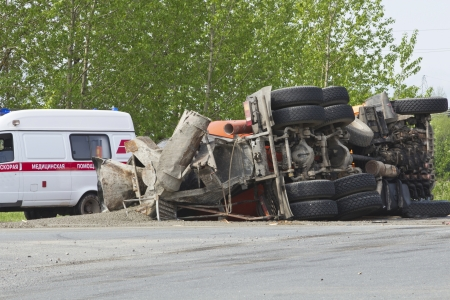overturned: truck carrying cement collided at the intersection with another truck and overturned Stock Photo