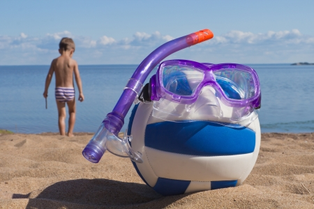 pastimes: the concept of a volleyball ball and a set of swimming at the sandy beach Stock Photo
