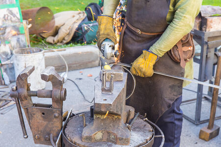 forger: blacksmith forges metal body on the street Stock Photo