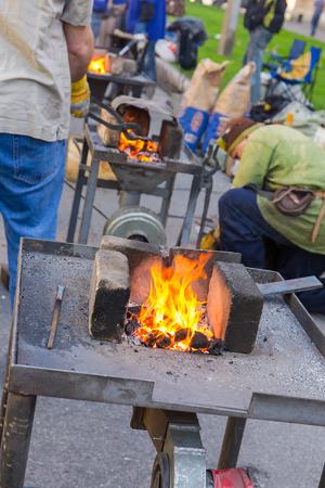 forgeman: blacksmith forges metal body on the street Stock Photo