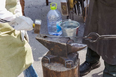 ancient blacksmith: blacksmith forges metal body on the street Stock Photo