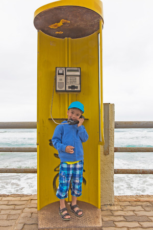 European boy  is talking on the phone, the yellow phone booth photo