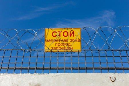 sign prohibiting passage on the fence with barbed wire photo