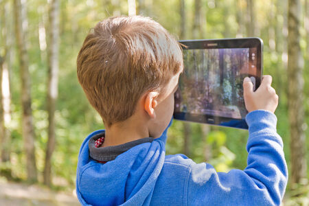 Happy little child holding tablet pc, outdoors.  Learning with modern technology. photo