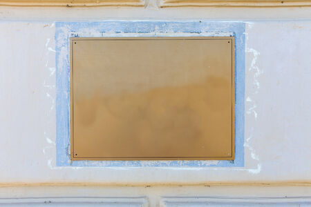 Old brass yellow metal plate framed and nailed on white stone wall background