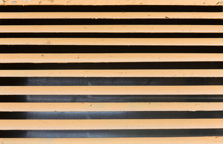 yellow steel ventilation grille on the wall of a building photo