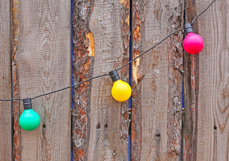 Electric garlands on a wooden fence. Festive background. photo
