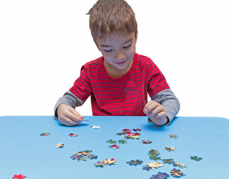 European boy playing with puzzle, early education concept