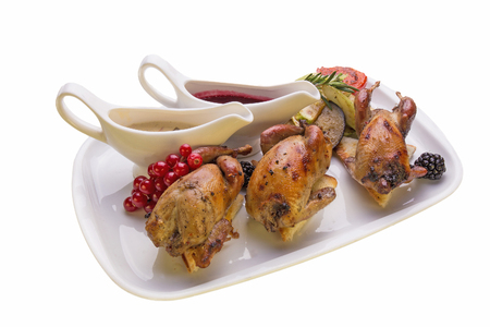 cornish: Roasted quail with vegetables on white background