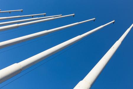 unoccupied: empty white flag poles against blue sky