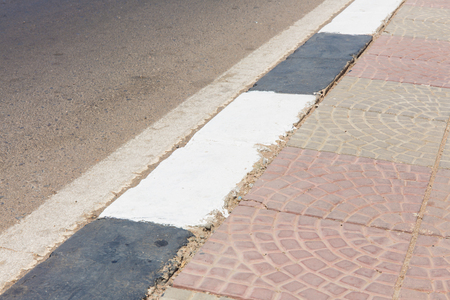 curb: white and black curb stone border and asphalt road Stock Photo