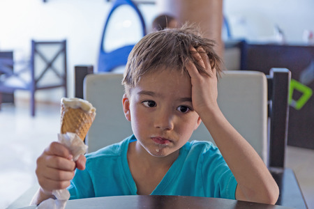 sad and pensive child with ice cream in hand Stock Photo