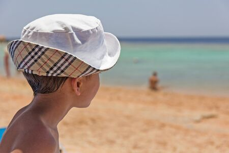 European boy in a hat looking at sea photo