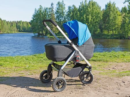 Baby stroller on the lake. The concept of lifestyle. Stock Photo