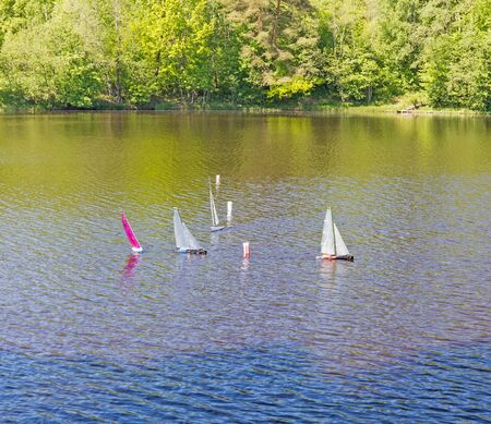 pleasure ship: small wooden sailing toy boats in the pond of park