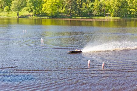 controlled: Close up radio controlled fuel engine toy boat in lake