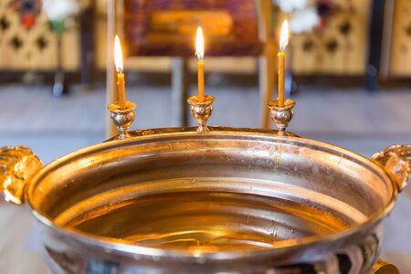 peaceful background: burning candles on the baptismal font for baptism Stock Photo