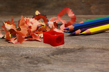 sharpening: Pencils with sharpening shavings on wooden background