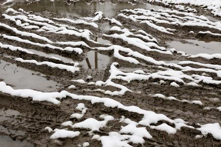 granizados: Snow slush on the road. Tire tracks on a snow covered road. Foto de archivo
