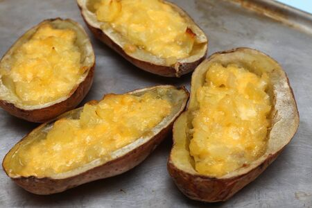 immediately: twice baked potatoes with parmesan cheese, cream cheese and butter in a metal pan immediately after baking in the oven.