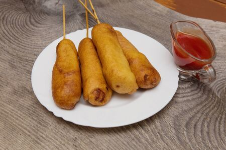 rustic food: Corn dog to do at home. A popular snack in the American fast fude. Stock Photo