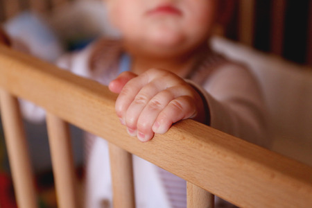 baby crib: handle to hold on to a wooden baby crib close-up