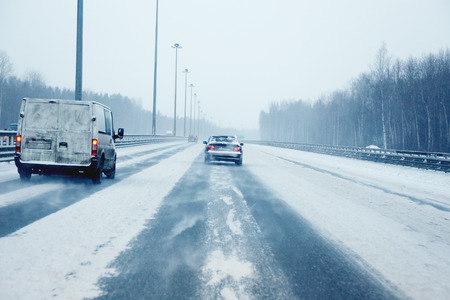 treacherous: highway covered with snow during a snowfall