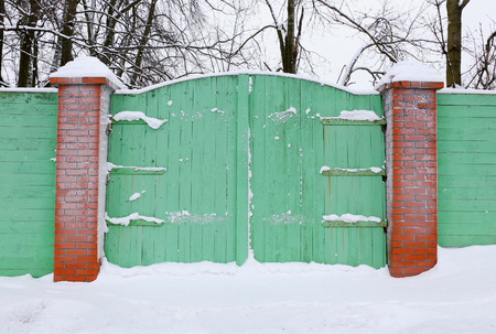 wicket door: old green wooden gate covered with snow
