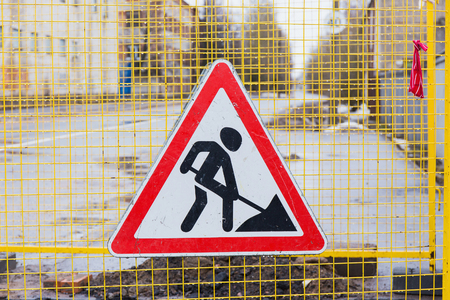 road works: Road works sign hanging on a fence close up