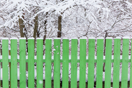 enclosing: wooden fence enclosing a green garden covered with snow